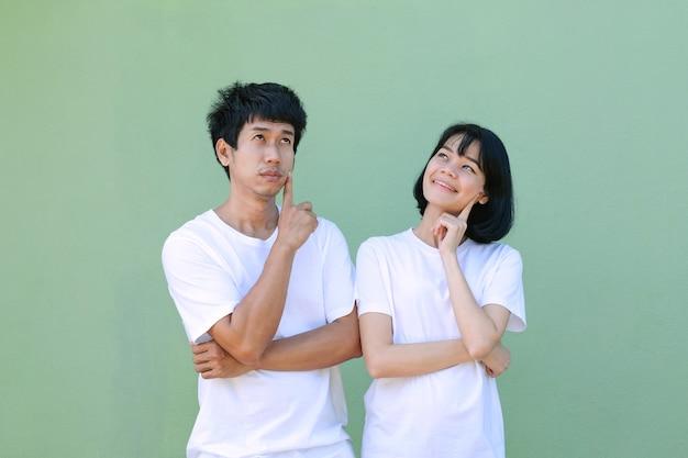 Um casal de asiáticos posa pensando e olhando de cima