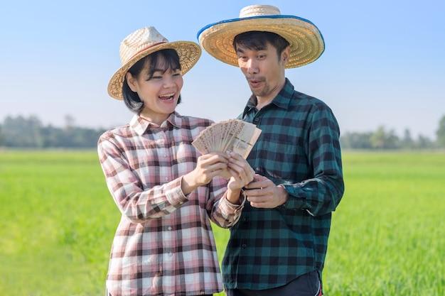 Um casal de fazendeiros asiáticos segurando uma nota de banco tailandês e olhando nossa cara de surpresa surpresa