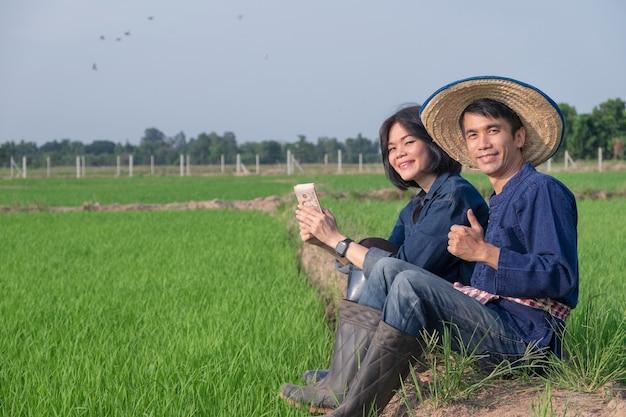 Um casal de fazendeiros asiáticos sentado e sorrindo segurando o dinheiro das notas tailandesas em uma fazenda de arroz verde