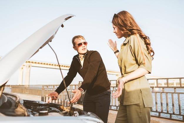 Um casal de homens e mulheres tem alguns problemas com o carro durante a viagem, consertar o motor, verificar