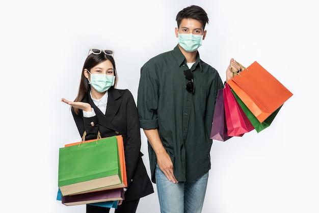 Um casal de homens e mulheres usando máscaras e carregando muitos sacos de papel para fazer compras