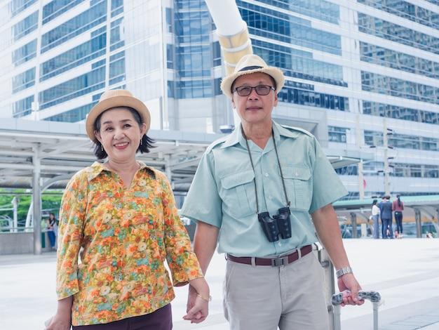 Um casal de idosos anda com as mãos enquanto viaja pela cidade