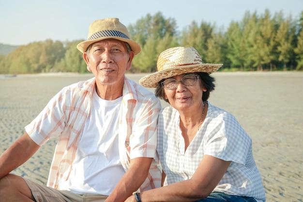 Um casal de idosos é um asiático. sentado e assistindo o pôr do sol na praia à beira-mar é feliz.