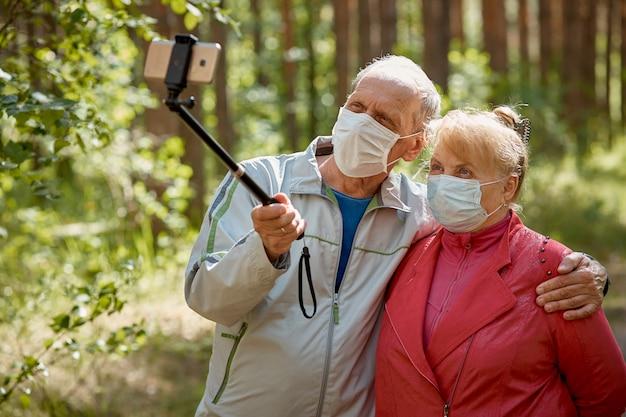Um casal de idosos em máscaras protetoras tira uma selfie em um smartphone e caminha no parque