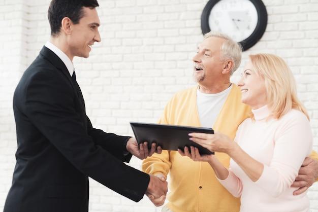 Um casal de idosos em uma recepção com um corretor de imóveis.
