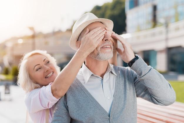 Um casal de idosos está andando na praça