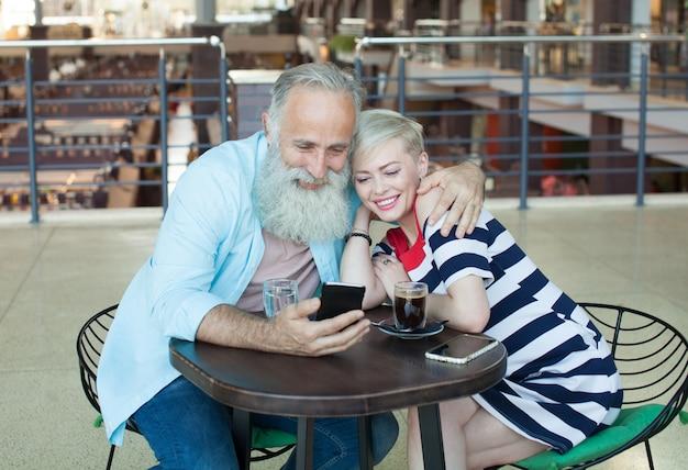 Um casal de idosos está conversando com seus filhos usando o telefone. ela está acenando para a filha na tela.