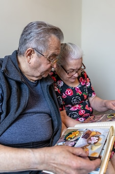 Um casal de idosos está olhando fotos em um álbum de família.