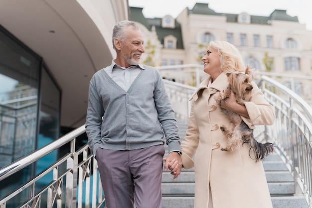 Um casal de idosos está sorrindo e olha para o outro.