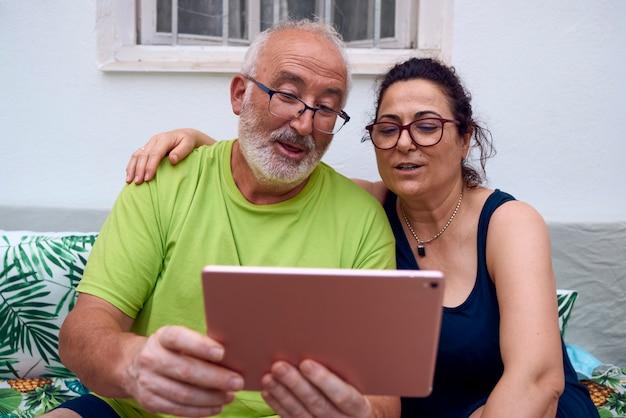 Um casal de idosos fazendo uma videochamada usando um tablet