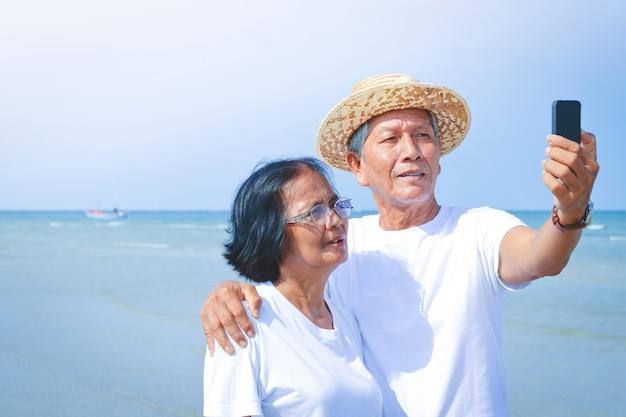 Um casal de idosos veste uma camisa branca para ir ao mar. em pé segurando o telefone para tirar fotos juntos