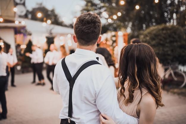 Um casal de jovens dançando em uma festa na rua