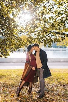 Um casal de lindos amantes passam tempo ao ar livre no dia de outono, uma linda mulher em um vestido vermelho e mod ...