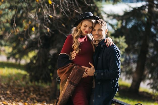 Um casal de lindos jovens futuros pais passam um tempo no parque de outono jovem grávida e um ...