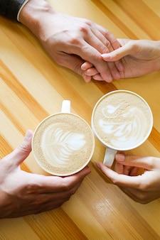 Um casal de mãos dadas em um café, bebendo café, nas mãos dos amantes sobre uma mesa de madeira.