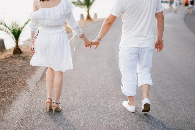 Um casal de namorados em roupas brancas caminha pela estrada perto do mar