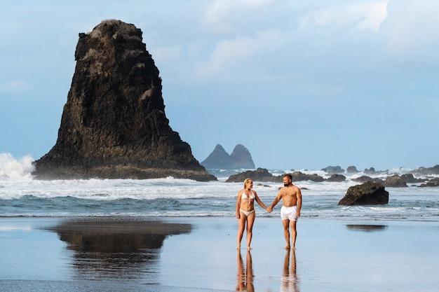 Um casal de namorados na praia de benijo, na ilha de tenerife. espanha.
