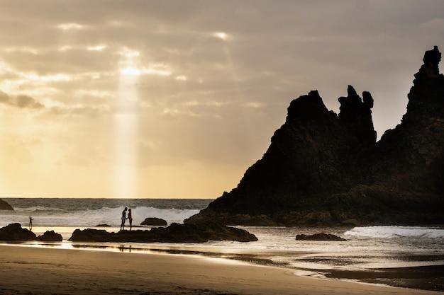Um casal de namorados na praia de benijo, na ilha de tenerife. espanha
