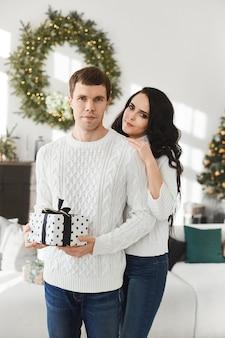 Um casal de namorados troca presentes de natal pela manhã