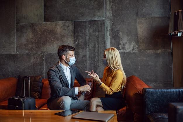Um casal de negócios com máscaras está sentado um ao lado do outro no saguão do hotel e tem uma conversa de negócios durante uma pandemia de coronavírus. simpósio, viagem de negócios