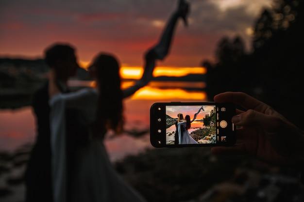 Um casal de noivos em pé ao lado de um rio. no fundo, a vila ao pôr do sol, atirando no telefone