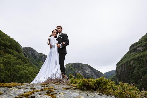Um casal de noivos em pé sobre uma rocha coberta de musgo