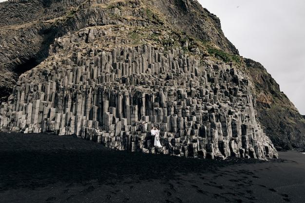 Um casal de noivos fica em pé em uma parede de pilares de pedra que os noivos abraçam em kekurs de basalto