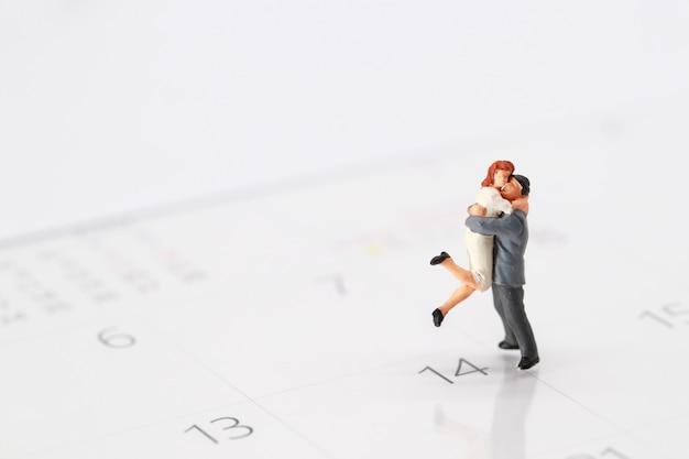 Um casal de pé no calendário em 14 de fevereiro