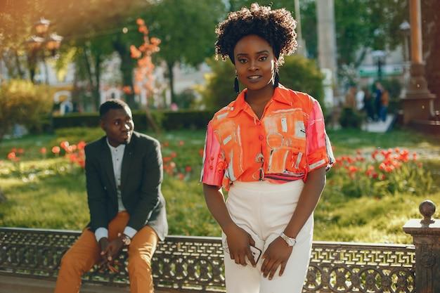Um casal de pele escura jovem e elegante, sentado em uma cidade ensolarada
