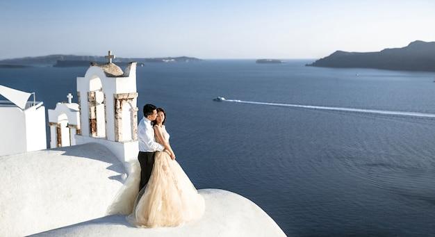 Um casal de pessoas recém-casadas em trajes bonitos aproveitando seus meses de lua de mel na grécia