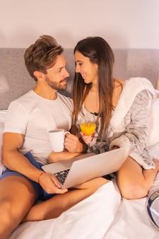 Um casal de pijama à procura de hotéis ou viagens do computador no café da manhã na cama do hotel, estilo de vida de um casal apaixonado.