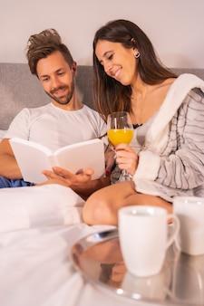 Um casal de pijama lendo um livro no café da manhã com café e suco de laranja na cama do hotel, estilo de vida de um casal apaixonado. foto vertical