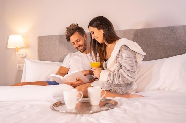 Um casal de pijama lendo um livro no café da manhã com café e suco de laranja na cama do hotel, estilo de vida de um casal apaixonado.