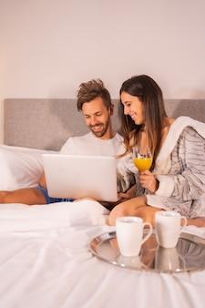 Um casal de pijama olhando para o computador no café da manhã de café e suco de laranja na cama do hotel, estilo de vida de um casal apaixonado.