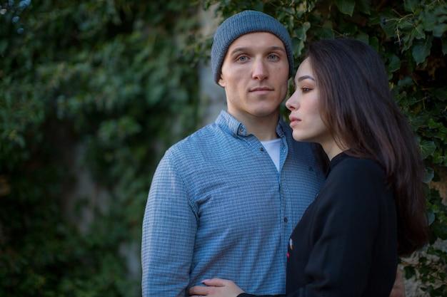 Um casal de pombinhos, cara e menina, abraçados perto de árvores verdes brilhantes, história de amor casal de amantes foto de alta qualidade
