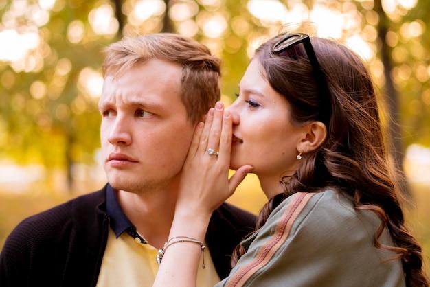 Um casal de rapazes e moças contam segredos um ao outro, sussurram no ouvido
