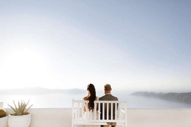 Um casal de recém casados pessoas desfrutando de seus meses de lua de mel na grécia no terraço sobre o mar