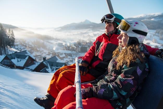 Um casal de snowboarders em um teleférico
