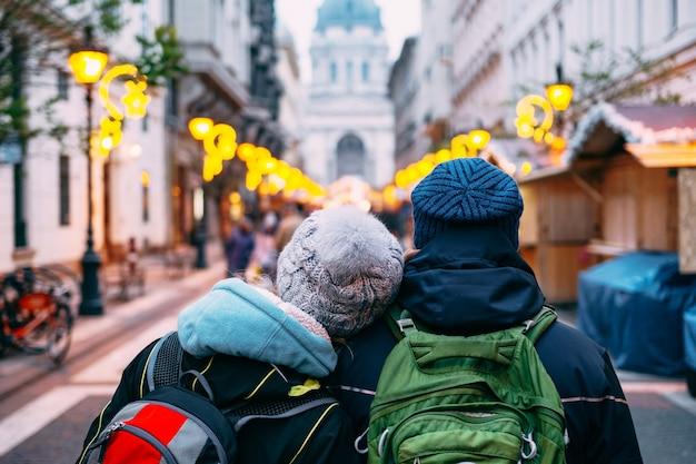 Um casal de turistas apaixonados caminha por budapeste no contexto da basílica de santo estêvão. foto de alta qualidade