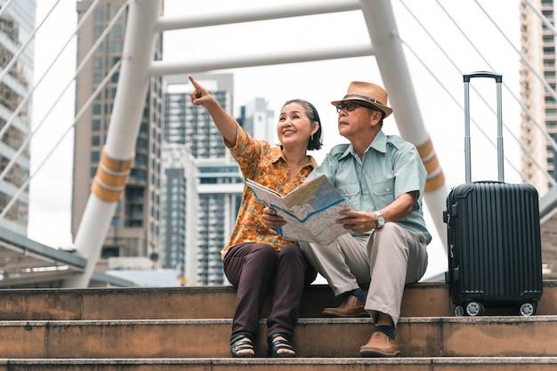 Um casal de turistas asiáticos idosos que visitam a capital alegremente e se divertem e olhando o mapa para encontrar lugares para visitar.