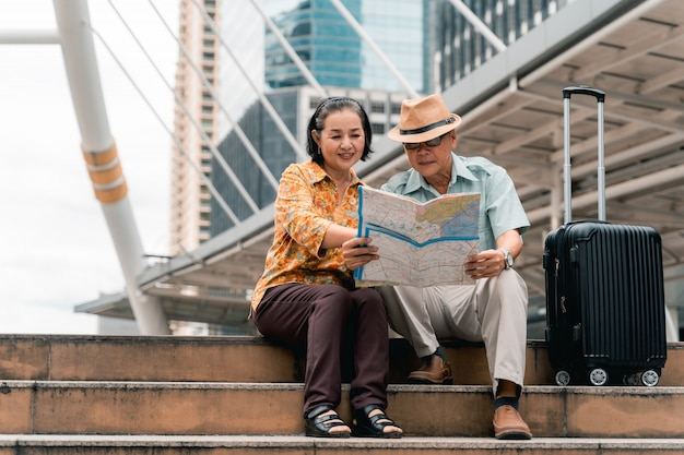 Um casal de turistas asiáticos idosos visitando a capital alegremente e se divertindo e olhando o mapa para encontrar lugares para visitar.
