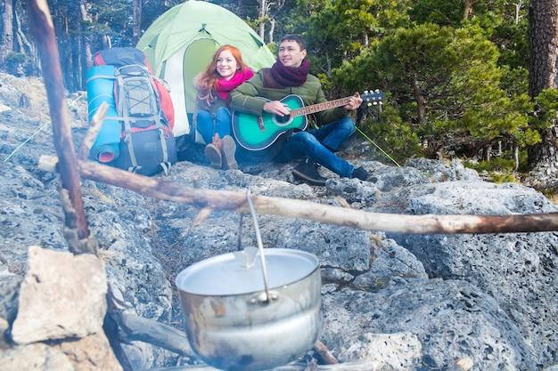 Um casal de turistas, mulher e homem sentado no acampamento na floresta e nas montanhas