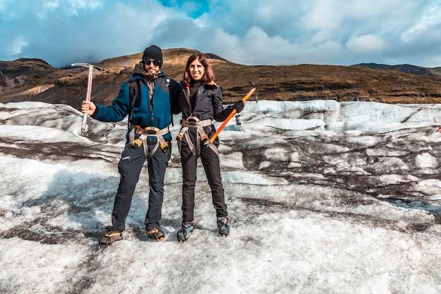 Um casal de turistas no gelo da geleira svinafellsjokull. islândia