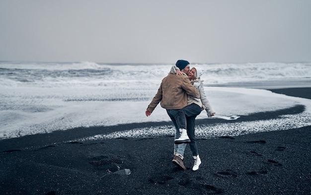Um casal de turistas se abraça e se divirta caminhando pela praia de areia negra vulcânica e admirando as grandes ondas do mar.