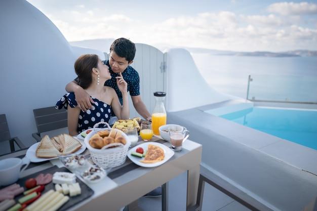 Um casal de turistas tomando café da manhã no terraço do hotel ao ar livre