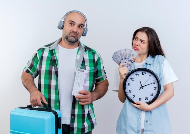 Um casal de viajantes adultos tristes usando fones de ouvido segurando passagens e uma mala, olhando a mulher segurando dinheiro e um relógio olhando para ele