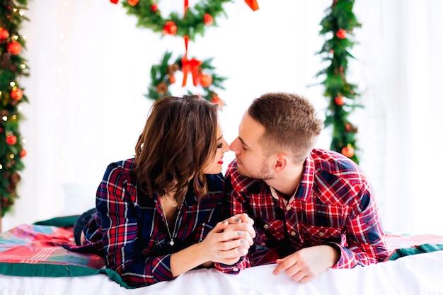 Um casal deitado em uma cama com enfeites de natal e fechou os olhos