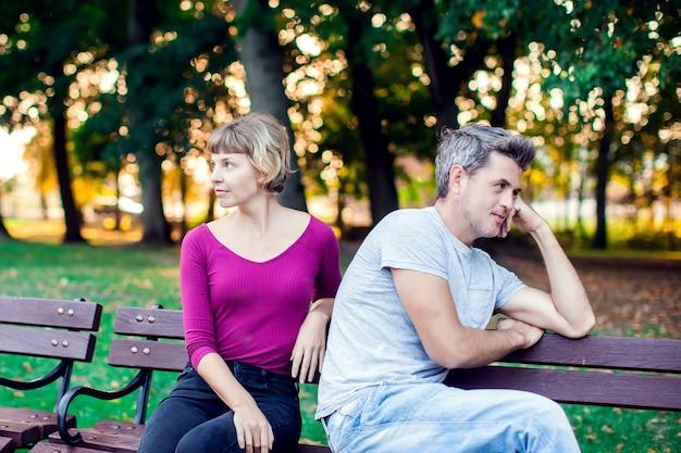 Um casal discutindo enquanto está sentado no banco do parque. problemas no relacionamento.