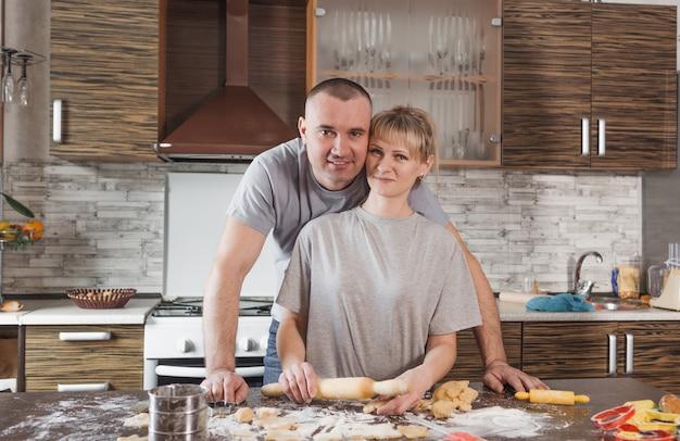 Um casal durante a preparação de biscoitos fica perto da mesa da cozinha em que uma grande quantidade de farinha é espalhada.