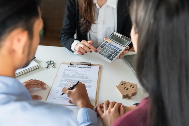 Um casal e uma mulher de negócios com calculadora e documentos
